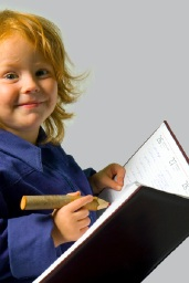 Image of smiling child writing in book
